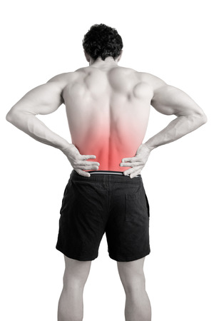 aching muscles: Male athlete with pain in his lower back, isolated in white. Red spot around painful area. Stock Photo