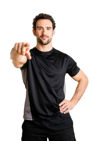 Personal trainer pointing at viewer, isolated in white photo