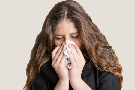 Pale sick woman with a flu, sneezing, in a clean background