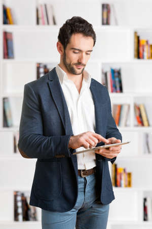 Casual Businessman Looking at a tablet, in an office photo