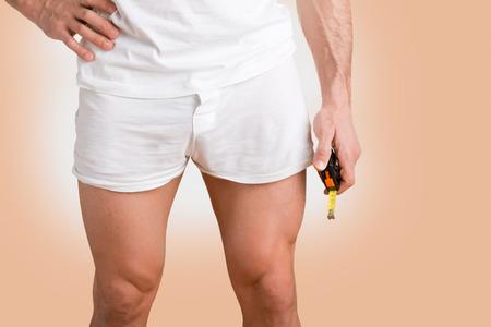 Concept van een man met een kleine penis met een meetlint in de hand Stockfoto