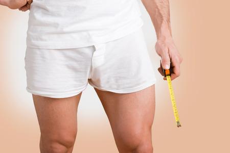 pene: Concepto de un hombre con un pene grande con una cinta métrica en la mano