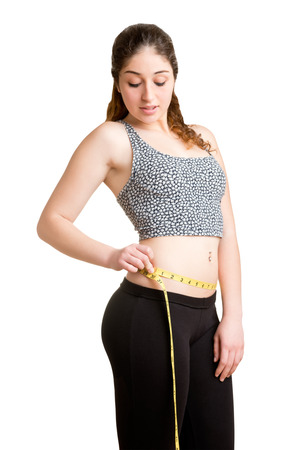 woman measuring: Woman measuring her waist with a yellow measuring tape, isolated in white Stock Photo