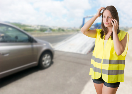 Woman talking on the phone wearing a reflector vest near her broken car photo