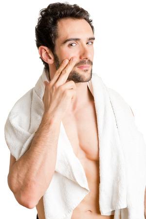 limpieza de cutis: Masculino aplica la crema hidratante en la cara, aislado en blanco