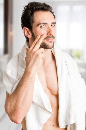 removing make up: Male applying moisturizer to her face in the bathroom