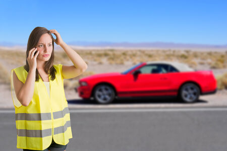 safety vest: Woman talking on the phone wearing a reflector vest next to her broken car