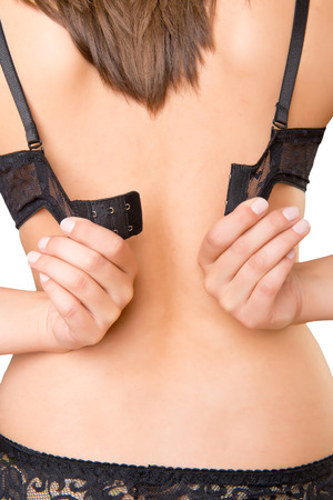 Closeup of womans back when shes taking of her clothes photo