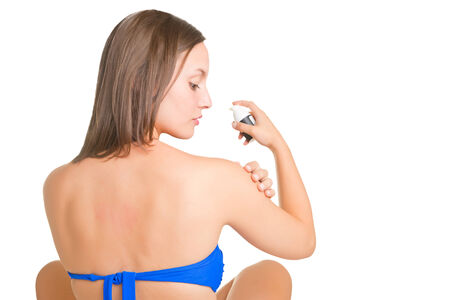 Woman applying sunscreen on her arm, isolated in white photo