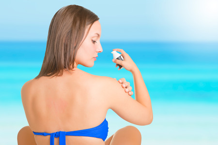 Woman applying sunscreen on her arm, in a beach  photo