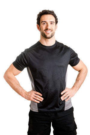 Personal trainer with is arms on his waist, isolated in white