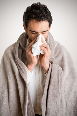 h1n1: Pale sick man with a flu, sneezing, in a clean background