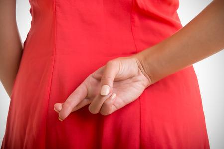 Zblízka zkříženými prsty za ženy zády