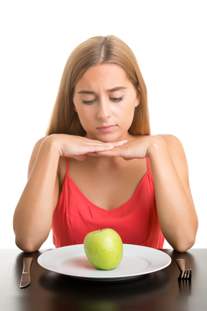 Woman contemplating a plate with a green apple, isolate in white photo