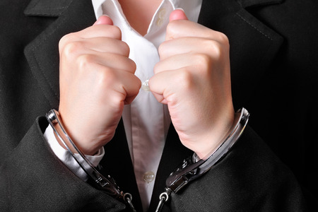 wrongdoing: Closeup of an handcuffed businessperson in a brown suit Stock Photo