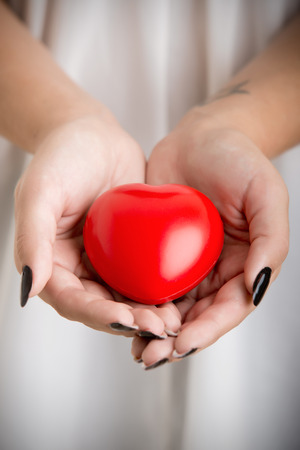 palpitations: Closeup of female hands holding a heart. Muted colors.