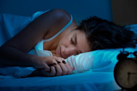 sono: Mulher que dorme em uma cama em um quarto escuro Imagens