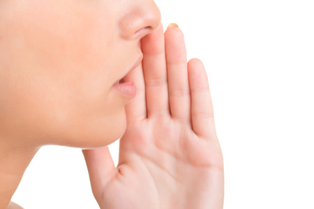 word of mouth: Close up of a womans mouth, telling a secret, isolated in white Stock Photo