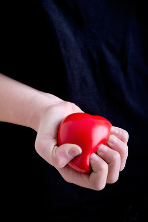 palpitations: Female Hands Holding a Heart in a dark background Stock Photo