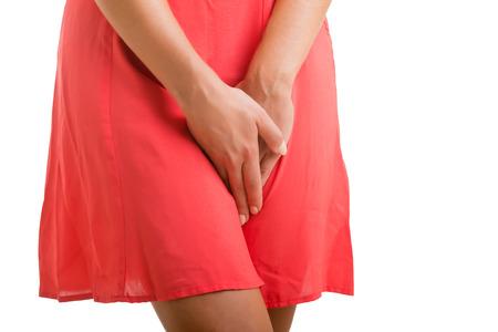 Zblízka se ženou s rukama drží rozkrok, v bílém