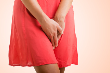 Close up of a woman with hands holding her crotch, isolated in a pink background
