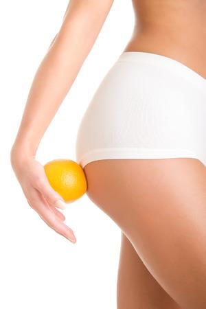 Vrouw die een oranje tegen haar dijen, geïsoleerd in het wit Stockfoto
