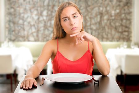 Hladový žena na dietu čekat s prázdnou deskou v restauraci Reklamní fotografie