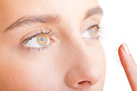 lentes de contacto: Primer plano de un rostro de mujer joven que inserta una lente de contacto, centrándose en los ojos, mirando a otro lado, aislados en blanco