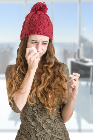 sniffle: Pale sick woman with a flu checking if she has a fever with a thermometer in an office
