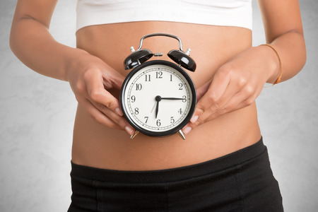biological: Concept of biological clock. Woman holding clock in front of her belly, isolated in white