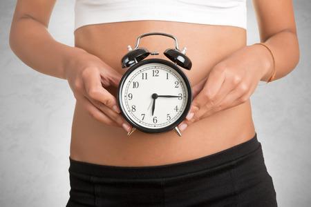 BIOLOGIA: Concepto de reloj biológico. Mujer que sostiene el reloj delante de su vientre, aislado en blanco