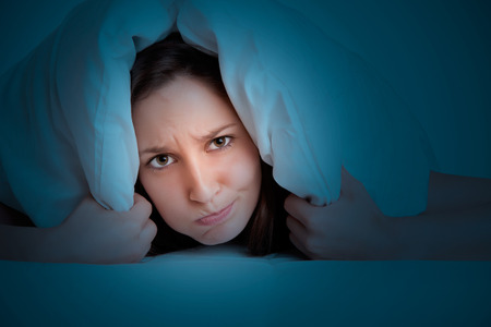 Woman with a pillow over her head, not wanting to get out of the bed in the dark Stock Photo