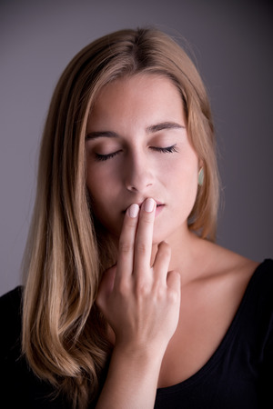Closeup of a woman with her finger over her mouth