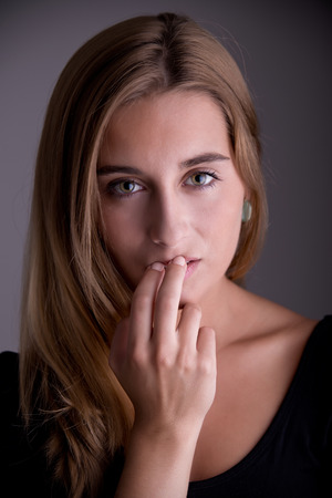 noiseless: Closeup of a woman with her finger over her mouth
