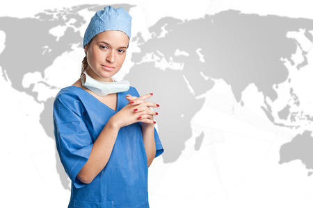 Young female surgeon with scrubs, holding a face mask on a map background photo