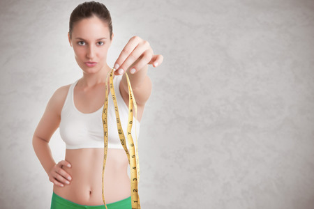 Woman holding a measuring tape in front of her Stock Photo