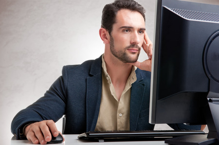 using the computer: Hombre que mira la pantalla de un ordenador, pensando en el trabajo a mano Foto de archivo
