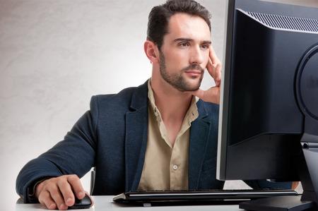 Man op zoek naar een computerscherm, na te denken over het werk bij de hand Stockfoto