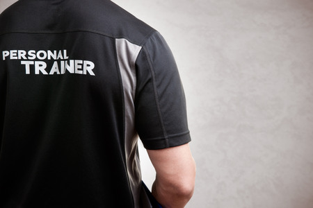 Personal Trainer, with his back facing the camera, in a grey background Banque d'images