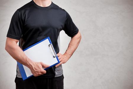 Personal Trainer, avec un pad à la main, isolé en gris Banque d'images - 43048601
