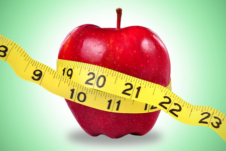 symbolize: Red apple and yellow measuring tape to symbolize an healthy diet and body weight control. Stock Photo