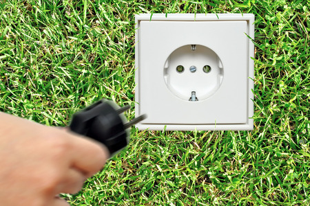electrical appliances: Hand connecting a plug to a socket on grass