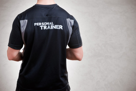 personal trainer: Back of a Personal Trainer isolated in grey Stock Photo