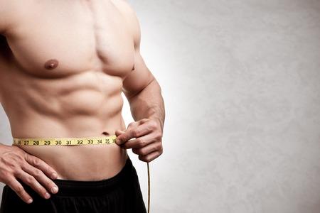cinta de medir: Hombre apto medir su cintura después de un entrenamiento en el gimnasio, aislado en un fondo gris Foto de archivo