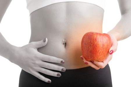 'flat stomach': Woman holding an apple with a hand on her abdomen. Focus on the apple. Stock Photo