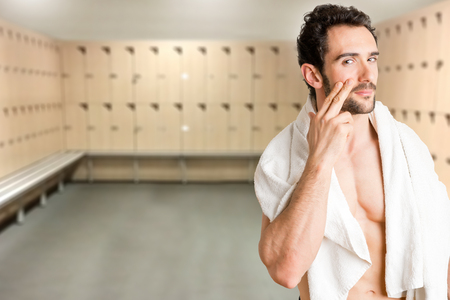 hair man: Male applying moisturizer to her face in a locker room