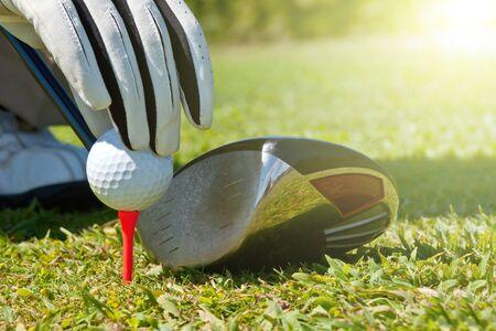golf glove: Hand placing a golf ball on a tee, next to a club.