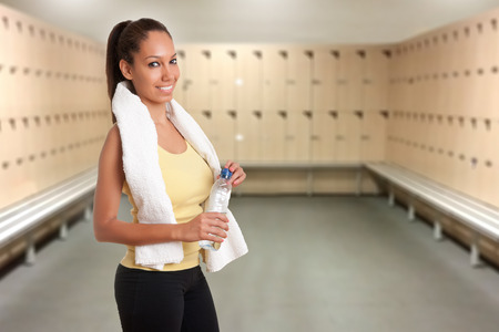 gym room: Woman holding a plastic bottle of water, dressed in sports clothes