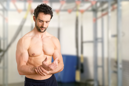 wrist pain: Male with pain in his wrist, isolated in a gym