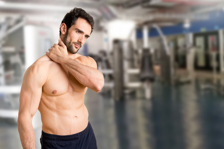 soreness: Athlete suffering from neck pain in a gym